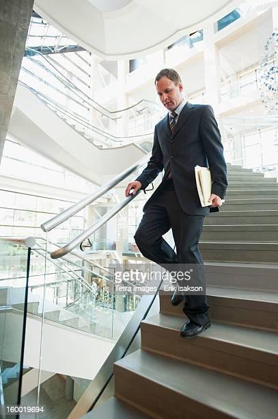 USA, Utah, Salt Lake City, Man walking down stairs in office