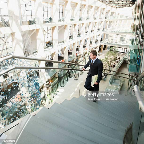 USA, Utah, Salt Lake City, Man walking up stairs in office