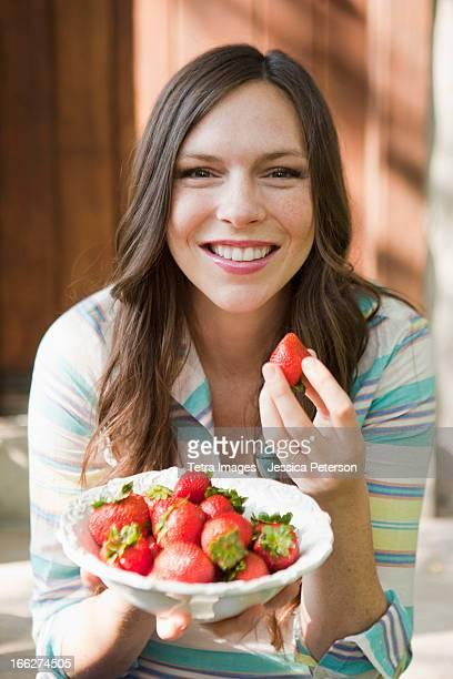 USA, Utah, Salt Lake City, portrait of mid adult woman eating strawberries