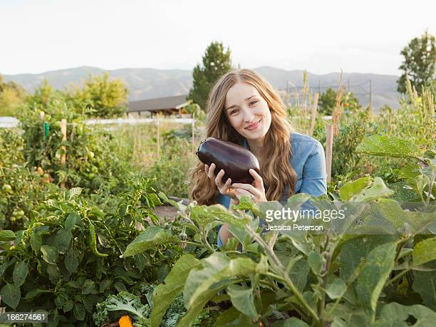 USA, Utah, Salt Lake City, Portrait of young woman harvesting eggplant