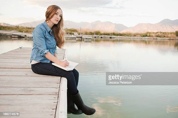 USA, Utah, Salt Lake City, Portrait of young woman sitting on jetty