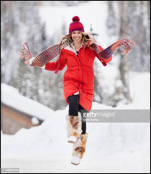 usa, utah, salt lake city, portrait of young woman skipping in snow - winter coat stock pictures, royalty-free photos & images