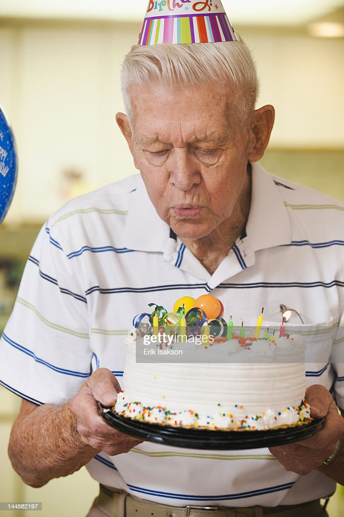USA Utah Salt Lake City Senior Man Blowing Candles On Birthday Cake