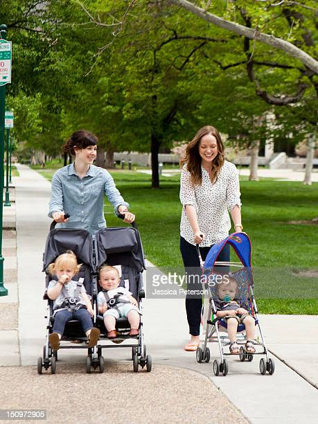 usa, utah, salt lake city, two young mothers walking with two baby boys (6-11 months) and toddler girl (2-3) in push prams - 2 5 months stock photos and pictures