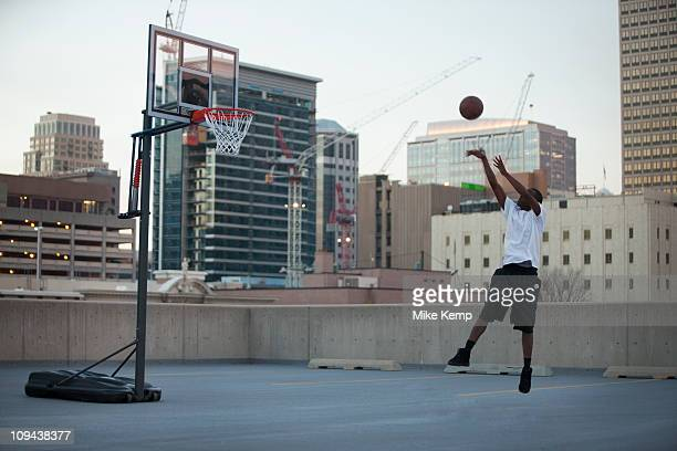 usa, utah, salt lake city, young man playing basketball - shooting baskets stock pictures, royalty-free photos & images
