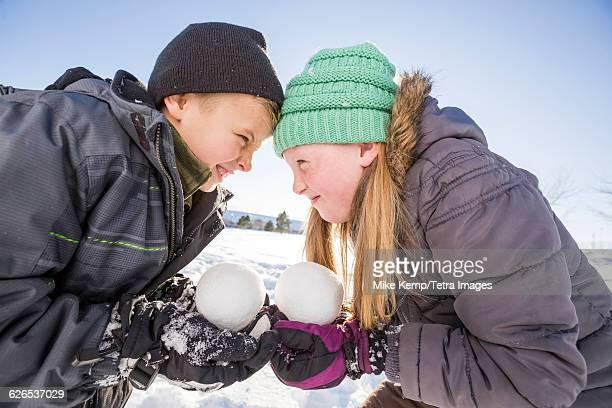 USA, Utah, Saratoga Springs, Children (8-9, 10-11) holding snowballs and touching foreheads