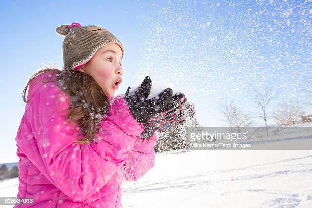 USA, Utah, Saratoga Springs, Girl (10-11) in pink jacket blowing snow
