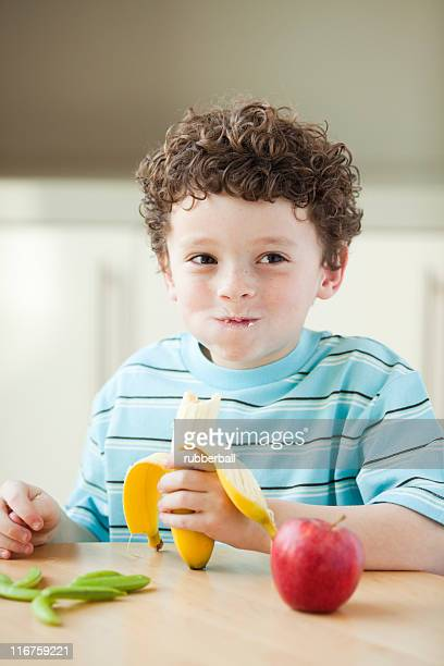 USA, Utah, Smiling boy (6-7) eating banana at kitchen table