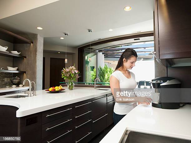 USA, Utah, St. George, Young woman making morning coffee