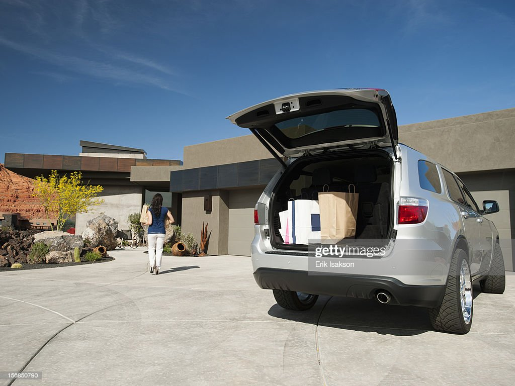 USA, Utah, St. George, Young woman unpacking shopping from car parked in yard : Stock Photo