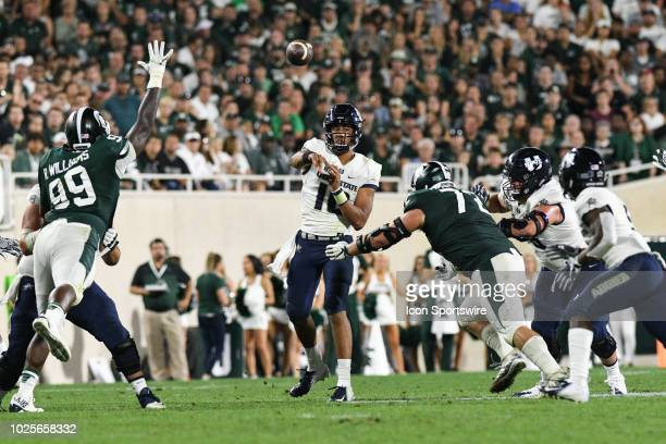 Utah State Aggies quarterback Jordan Love throws a pass through a tight window during a nonconference college football game between Michigan State...