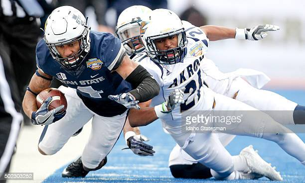 Utah State wide receiver Hunter Sharp is forced out of bounds by Akron cornerback Kris Givens and cornerback Bryce Cheek rear during the Famous Idaho...