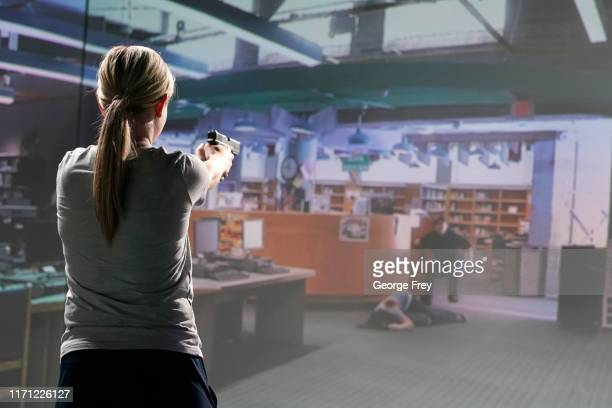 Utah teacher Holli Averett interact with a video simulator that creates an active shooter scenario in a school during a training session on September...