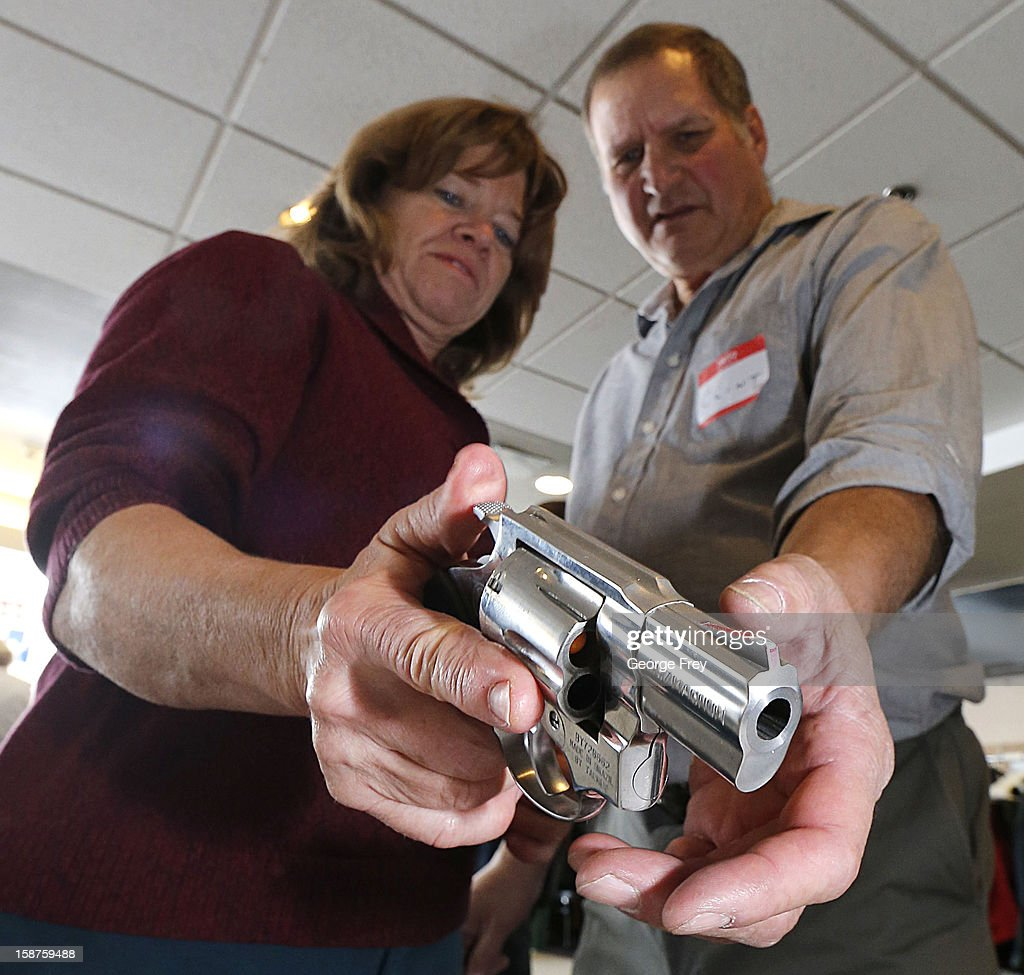 A Utah teacher is shown how to handle a handgun by instructor Clint Simon (R), at a concealed-weapons training class to 200 Utah teachers on December 27, 2012 in West Valley City, Utah. The Utah Shooting Sports Council said it would waive its $50 fee for concealed-weapons training for Utah teachers.