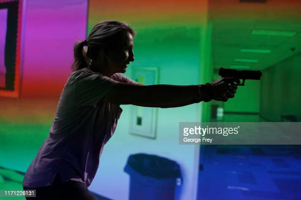 Utah teacher Natalie Bailey interact with a video simulator that creates an active shooter scenario in a school during a training session on...