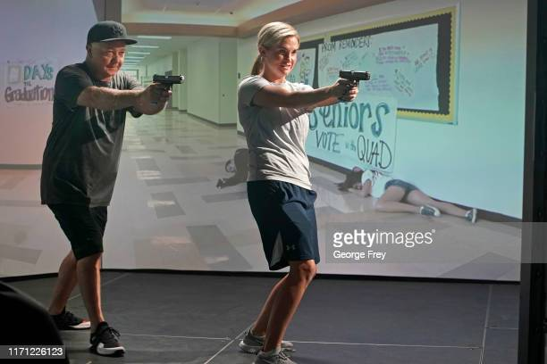 Utah teachers Anthony Bowden and Holli Averett interact with a video simulator that creates an active shooter scenario in a school during a training...