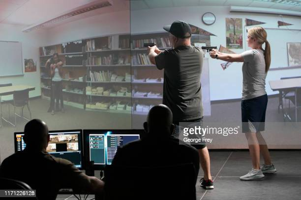 Utah teachers Anthony Bowder and Holli Averett interact with a video simulator that creates an active shooter scenario in a school during a training...