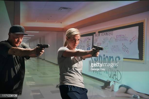 Utah teachers Anthony Bowdern and Holli Averett interact with a video simulator that creates an active shooter scenario in a school during a training...