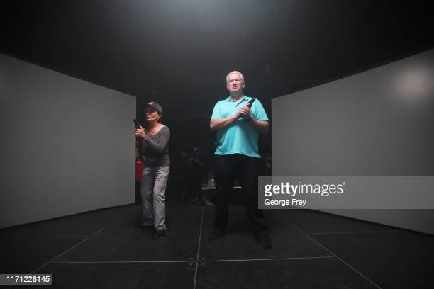 Utah teachers Coni Brooks and Tom Erekson , get ready to interact with a video simulator that creates an active shooter scenario in a school during a...