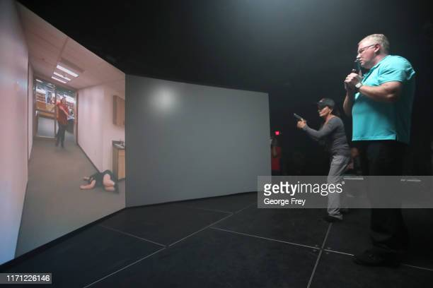 Utah teachers Coni Brooks and Tom Erekson , interact with a video simulator that creates an active shooter scenario in a school during a training...