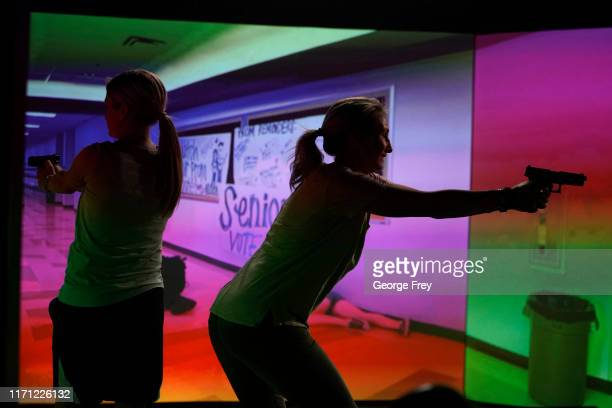 Utah teachers Holli Averett , and Natalie Bailey interact with a video simulator that creates an active shooter scenario in a school during a...
