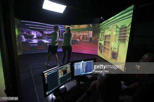 Utah teachers Holli Averett and Natalie Bailey interact with a video simulator that creates an active shooter scenario in a school during a training...