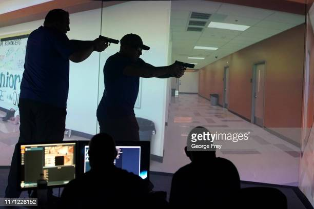 Utah teachers interact with a video simulator that creates an active shooter scenario in a school during a training session on September 25 2019 in...