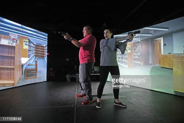 Utah teachers John Anderson and Elynn Jackson interact with a video simulator that creates an active shooter scenario in a school during a training...