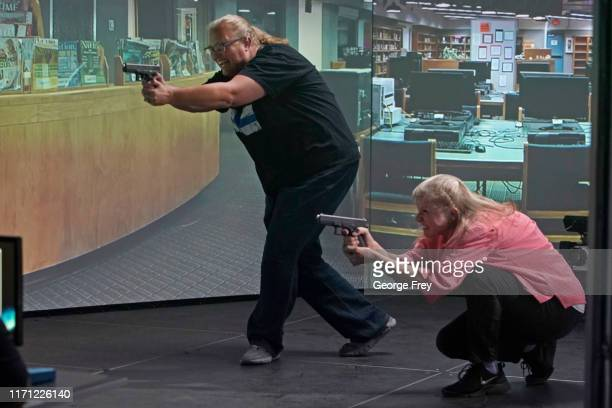 Utah teachers Sarah Scott and Shelly Brailsford , interact with a video simulator that creates an active shooter scenario in a school during a...