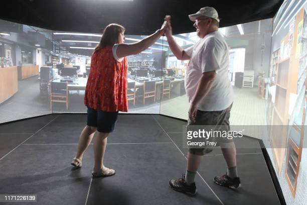Utah teachers Tiffani Erickson , and Bob Stutz high five after the did a video simulator that creates an active shooter scenario in a school during a...