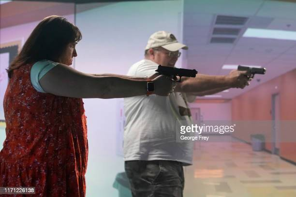 Utah teachers Tiffani Erickson , and Bob Stutz interact with a video simulator that creates an active shooter scenario in a school during a training...