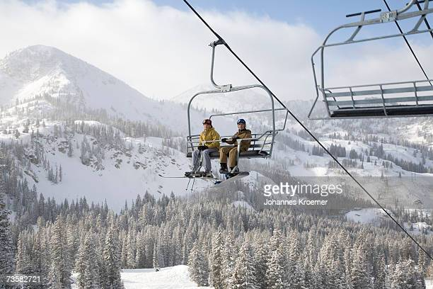 usa, utah, teenage girl and boy (13-16) sitting on ski lift at brighton ski resort - ski lift stock pictures, royalty-free photos & images