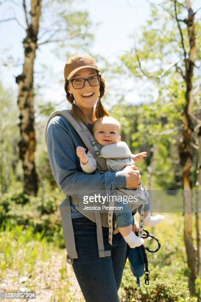 usa, utah, uinta national park, portrait of smiling woman with baby son (6-11 months) in baby carrier in forest - 6 11 months stock pictures, royalty-free photos & images