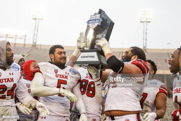 Utah Utes linebacker Kavika Luafatasaga offensive lineman Salesi Uhatafe and tight end Harrison Handley hold up the Zaxby's Heart of Dallas Bowl...