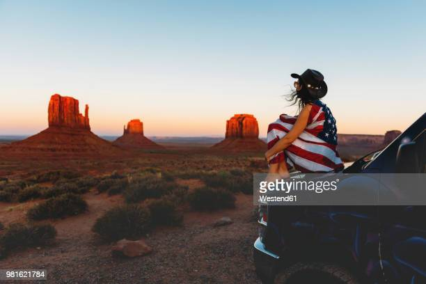 usa, utah, woman with united states of america flag enjoying the sunset in monument valley - usa stock pictures, royalty-free photos & images