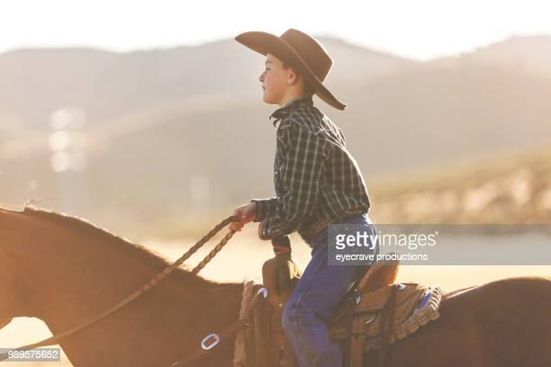 rodeo estampida rodeo montar a caballo, arreo de ganado y utah juventud vaquero occidental al aire libre - pantalón de cuero fotografías e imágenes de stock