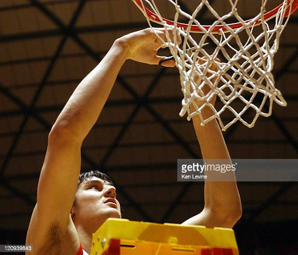 Utahs Andrew Bogut takes a piece of the net following their victory over BYU at the Jon Huntsman Center in Salt Lake City Utah Saturday Feb 26 2005...
