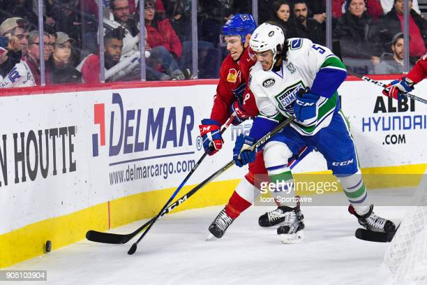 Utica Comets defenceman Jalen Chatfield and Laval Rocket right wing Adam Cracknell battle hard to get to the pcuk first during the Utica Comets...