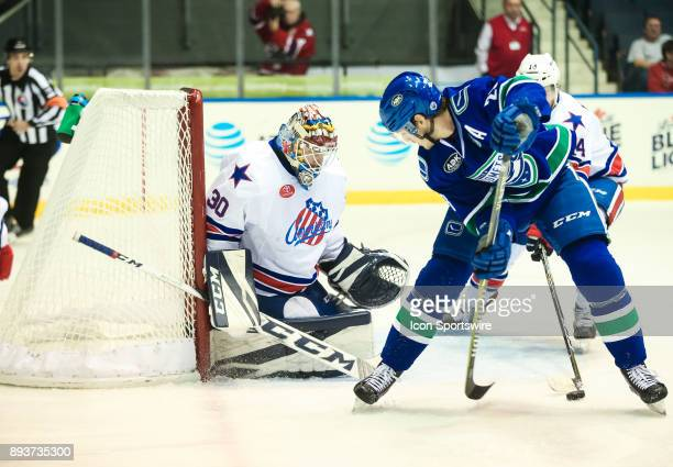 Utica Comets defenseman Patrick Wiercioch tries to sneak the puck past Rochester Americans goalie Linus Ullmark during an AHL game between the Utica...