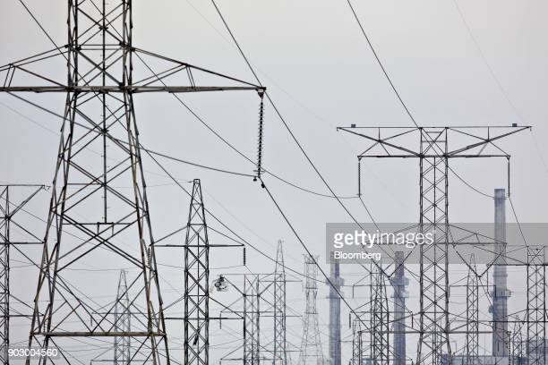 A utility crew works on a transmission tower near the NRG Energy Inc Will County Generating Station a coalfired power plant in Romeoville Illinois US...