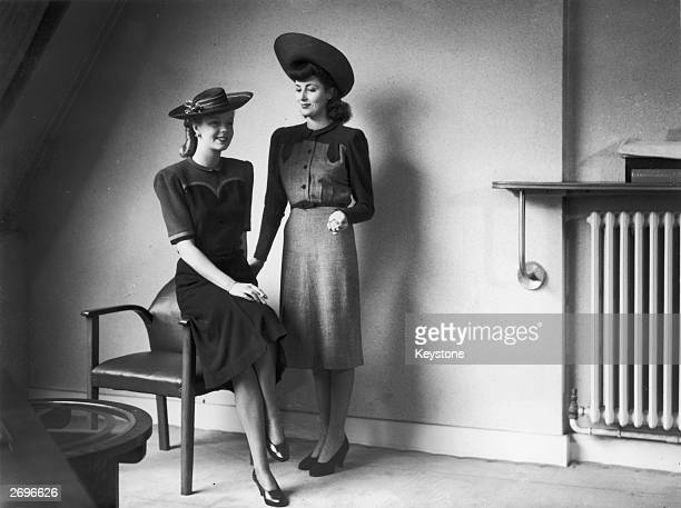 Utility dresses designed by Norman Hartnell for Berketex. On the left is a navy blue wool dress with elbow length sleeves. The yoke is scarlet with...