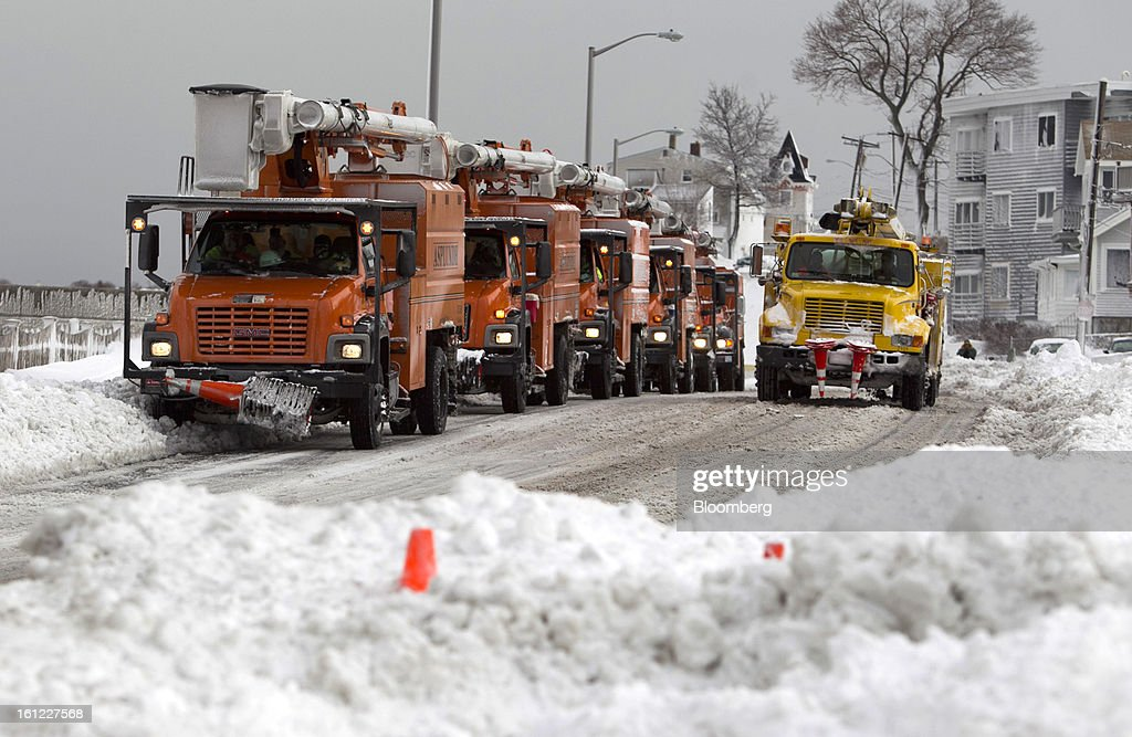 Utility trucks sit idle along Winthrop Shore Drive after Winter Storm Nemo in Winthrop, Massachusetts, U.S., on Saturday, Feb. 9, 2013. More than two feet of snow fell on parts of the U.S. Northeast as high winds left hundreds of thousands of people in the region without power, closed highways and forced the cancellation of 4,700 flights. Photographer: Kelvin Ma/Bloomberg via Getty Images