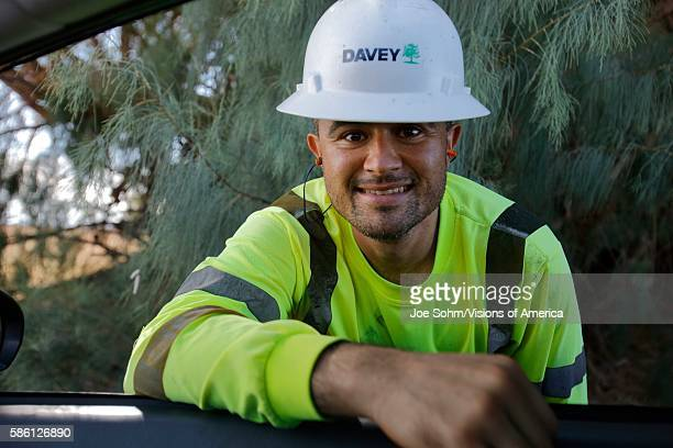 Utility worker in green shirt smiles while leaning into car near Barstow CA