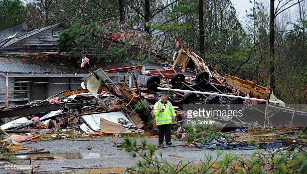 A utility worker stands in front of the site on Alabama Highway 71where three people were killed and one critically injured when their mobile home...