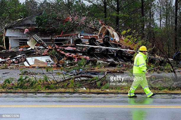 A utility worker walks past the site on Alabama Highway 71where three people were killed and one critically injured when an earlymorning tornado tore...