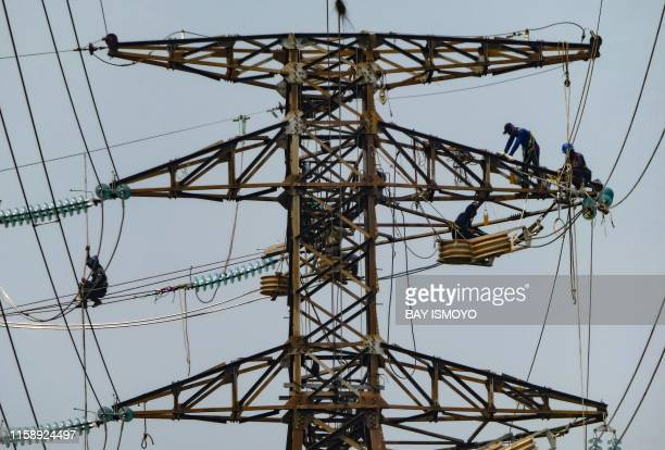 TOPSHOT Utility workers balance on a highvoltage utility tower in Jakarta on August 1 2019