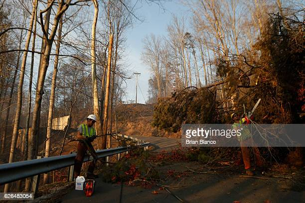 Utility workers remove a tree that fell across a road while nearby homes smolder after a wildfire November 29 2016 in Gatlinburg Tennessee Thousands...