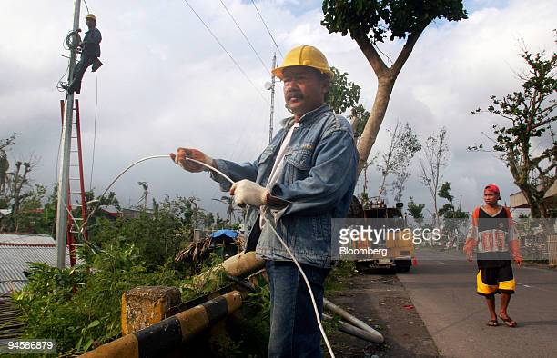Utility workers repair downed power transmission lines resulting from Typhoon Durian in the town of Daraga in Albay province southeast of Manila in...