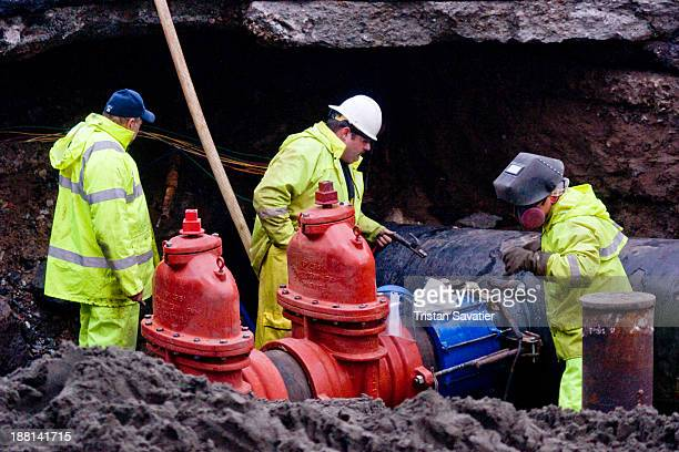 Utility workers repairing a broken water main at Division st and 10th st in SoMa district . The contractors installed two large cut-off valves on an...