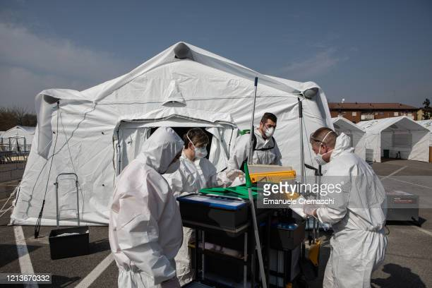 Utility workers wearing protective suits stand in front of a tent at a Samaritan's Purse Emergency Field Hospital on March 20 2020 in Cremona near...